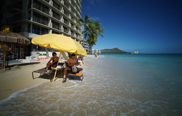 Visitors sit on beach as tides rise fronting Castle Waikiki Shore as larger surf might cause more inundation of Waikiki shoreline. 24 may 2017