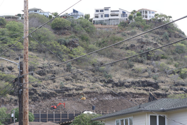 Excavators and tractors pound away at mountainside above 5209 Keikilani Circle.