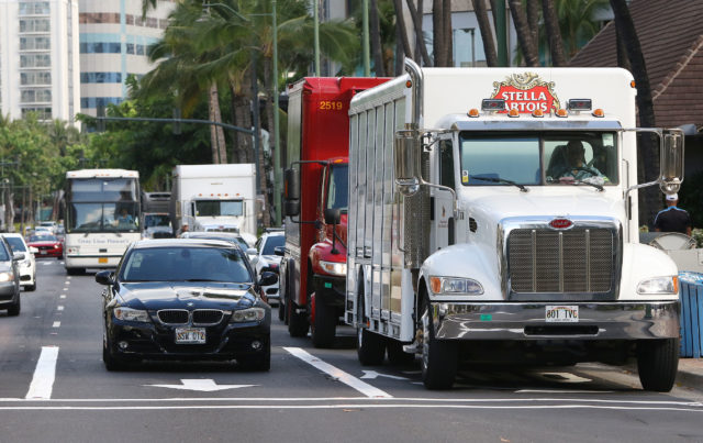 Kalakaua Avenue snarled with delivery trucks and traffic in the morning.