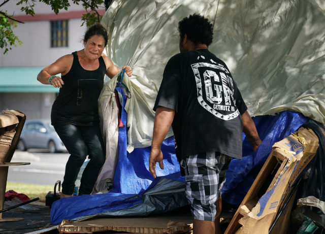 Renee (no last name) screams out while trying to quickly disassemble her tent before city and county workers sweep her tent away on a median on State of Hawaii land along Nimitz. Honolulu Harbor. 5 june 2017