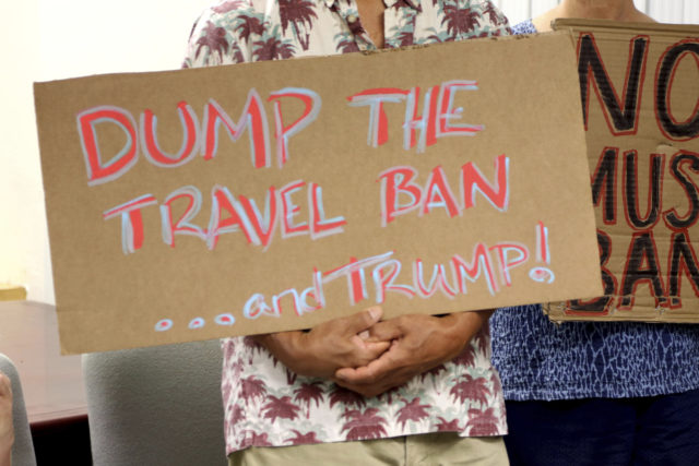 """FILE- In this June 30, 2017, file photo, critics of President Donald Trump's travel ban hold signs during a news conference with Hawaii Attorney General Douglas Chin in Honolulu. A federal judge in Hawaii on Thursday, July 6, left Trump administration rules in place for a travel ban on citizens from six majority-Muslim countries. U.S. District Court Judge Derrick Watson denied an emergency motion filed by Hawaii asking him to clarify what the U.S. Supreme Court meant by a """"bona fide"""" relationship in its ruling last month. (AP Photo/Caleb Jones, File)"""