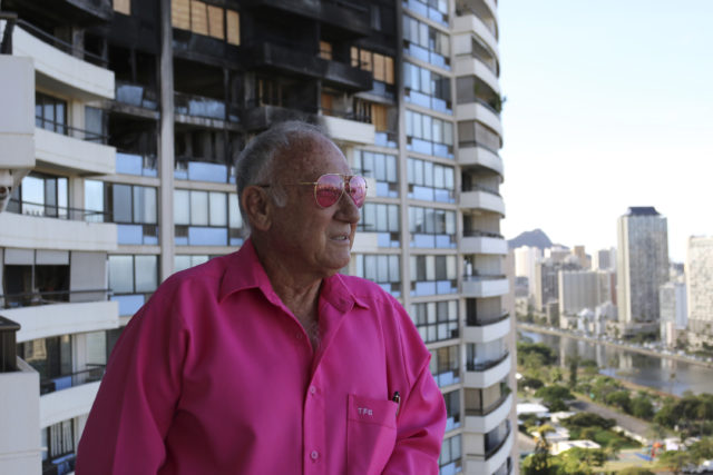 In this July 27, 2017 photo, Tom Schmidt stands in front of fire damage at the Marco Polo residential high-rise in Honolulu. The building, where three people died in a recent fire did not update its fire alarm system to meet the latest safety standards. City records obtained by The Associated Press show no upgrades were made after an engineering firm recommended them after another fire four years ago. Schmidt, who lives on the 26th floor where the fire broke out, said he's overwhelmed with joy that he's still alive. (AP Photo/ Cathy Bussewitz)