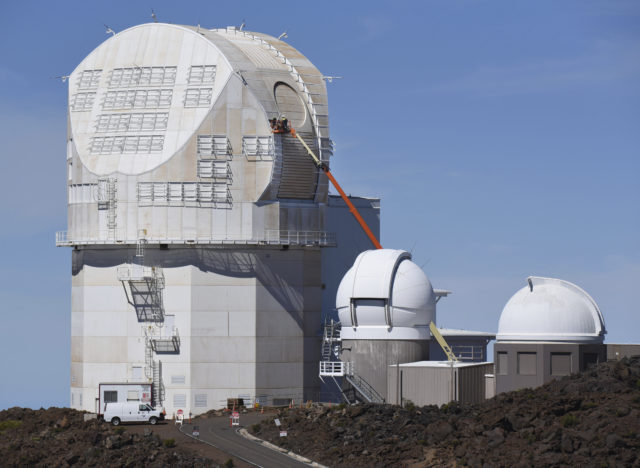 FILE - In this June 24, 2016, file photo, workers use a lift to scale the exterior the Daniel K. Inouye Solar Telescope at the summit of Haleakala. Five arrests were made early Wednesday, Aug. 2, 2017, when about 100 people tried to block an equipment convoy for a solar telescope being built on a Hawaii mountain held sacred by Native Hawaiians. The State Department of Land and Natural Resources says police arrested three women and two men. Construction of the Daniel K. Inouye Solar Telescope on Maui's Haleakala is nearly complete, unlike another embattled telescope planned for a different Hawaii mountain. (Matthew Thayer/The News via AP, File)