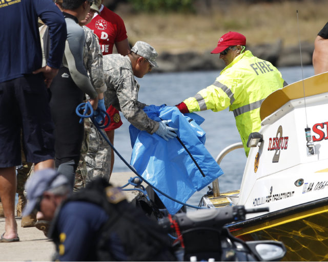 Water safety officials hand over possible debris from an Army UH-60 Black Hawk helicopter crash to military personnel stationed at a command center in a harbor, Wednesday, August 16, 2017 in Haleiwa, HI. An Army helicopter with five on board crashed several miles off Oahu's North Shore late Tuesday. Rescue crews are searching the waters early Wednesday. (AP Photo/Marco Garcia)