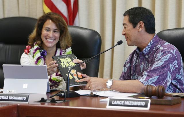 Board of Education Chair Lance Mizumoto gifts Pidgin to Max and Pidgin to Da Max Hana Hou books to Superintendent Christina Kishimoto at Board of Education meeting.