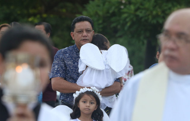 Roland Sandia carries his grand daughter in the procession held at Assumption of Our Lady Biba Santa Maria fiesta. Sandia alleges Archbishop Apuron sexually abused he and other altar servers