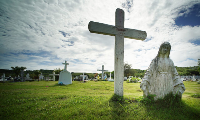 Guam Holy Cross Catholic Cemetery with a partially buried figure of Mary.