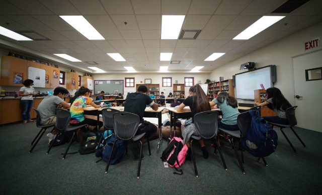 Mrs. Amy Perruso discusses with her 9th grade students about two Bayonet Constitution political cartoons from 1887 in her Mililani High School class.