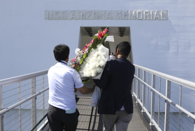 Members of Nippon Izokukai, the Bereaved Family Association of Japan, carry flowers onto the USS Arizona Memorial in Pearl Harbor, Hawaii, Thursday, Sept. 21, 2017. Dozens of descendants of Japanese soldiers killed in World War II visited Pearl Harbor on Thursday to pay respects to American war dead. Nippon Izokukai sent about 36 children, grandchildren and other relatives of fallen Japanese soldiers to the U.S. to mark the 70th anniversary of the group's founding. With the rusted hull of the USS Arizona beneath them, the group laid flowers and a wreath at the memorial after touring the Pacific Aviation Museum and the USS Missouri at Pearl Harbor. (AP Photo/Caleb Jones)