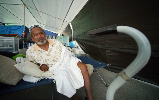 Hale Kikaha resident Kamehameha interviewed on his cot that he sleeps on under tarp/tent. Kailua Kona, Hawaii.