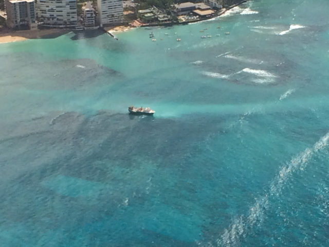 In this photo provided by the U.S. Coast Guard, a fishing vessel sits grounded on a reef off the shore of Honolulu, Wednesday, Oct. 11, 2017. The U.S. Coast Guard rescued over a dozen foreign fishermen and their American captain from the 79-foot (24-meter) U.S.-flagged commercial fishing vessel that ran aground off the shore of Waikiki on Tuesday night. (John Manganaro/U.S. Coast Guard via AP)