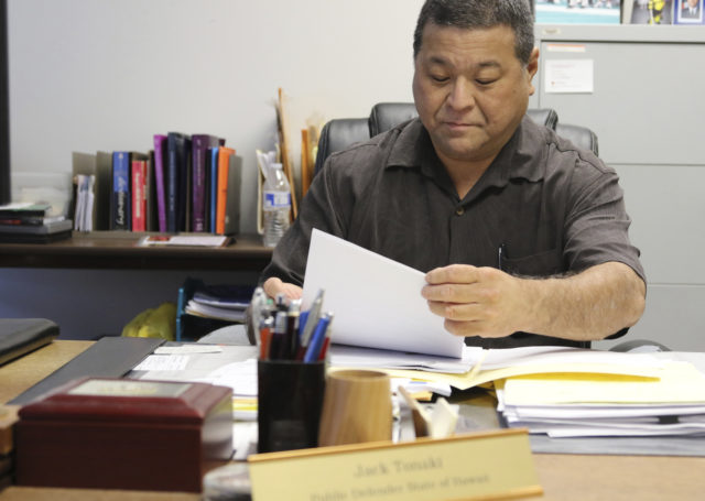 Hawaii State Public Defender Jack Tonaki looks over documents in his office in Honolulu on Thursday, Oct. 26, 2017. Hawaii's public defender is reviewing the criminal cases handled by four Honolulu police officers and a deputy city prosecutor to uncover any possible wrongdoing after a U.S. grand jury indicted them on allegations including planting evidence, falsifying reports and lying to federal investigators in a corruption probe. (AP Photo/Jennifer Sinco Kelleher)