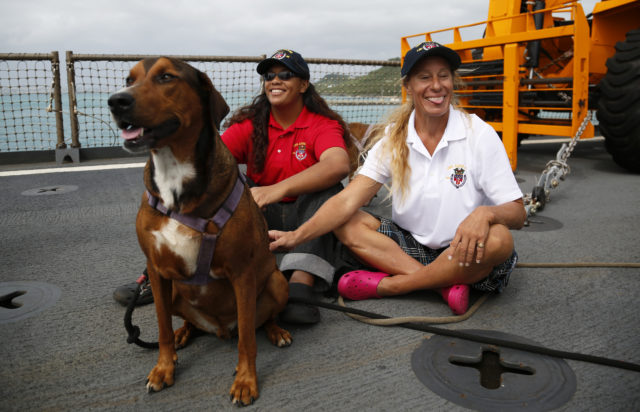 Jennifer Appel, right, and Tasha Fuiava sit with their dogs on the deck of the USS Ashland Monday, Oct. 30, 2017, at White Beach Naval Facility in Okinawa, Japan. The U.S. Navy ship arrived at the American Navy base, five days after it picked up the women and their two dogs from their storm-damaged sailboat, 900 miles southeast of Japan. (AP Photo/Koji Ueda)