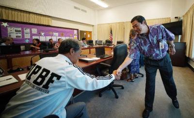 Board of Education Chair Lance Mizumoto greets board member Hubert Minn. file photograph 8/1/17