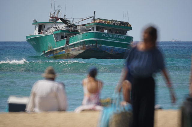 Pacific Paradise is shown stuck on reef offshore Kaimana Beach as people enjoy the beach in foreground.