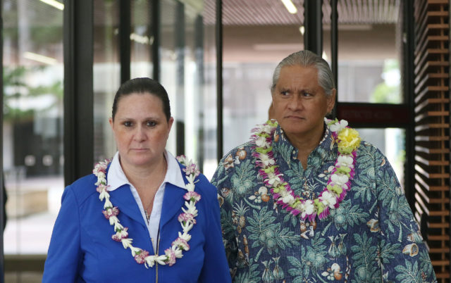 Retired HPD Chief Louis Kealoha and Katherine Kealoha bedecked with lei as they exit US District Court.