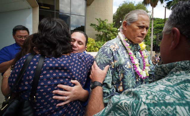 Retired HPD Chief Louis Kealoha and Katherine Kealoha bedecked with lei as they exit US District Court and embrace supporters.
