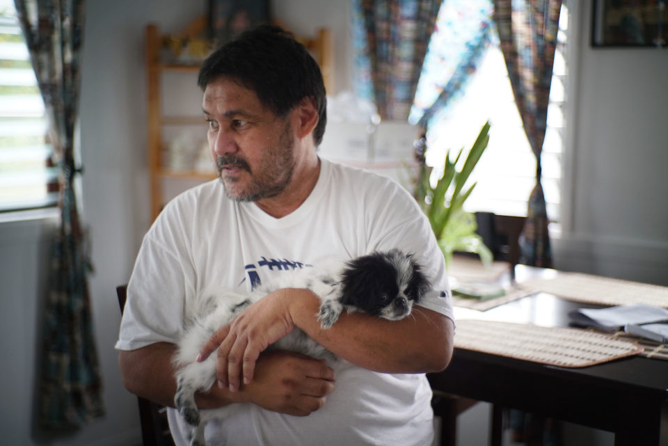 Jay Dela Pina holds his daughters dog named in his home located in Hilo, Hawaii. John Hill story on Workers comp.