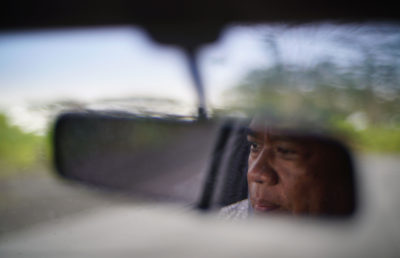 Michael Makekau seen thru his rear view mirror as he drives to the old landfill location where he was sickened by mold from an airconditioner at the Hilo landfill.