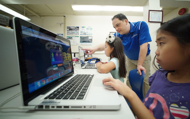 Momilani Elementary Tech Lab class instructor/teacher Shane Asselstine assists with his 4th graders in class.