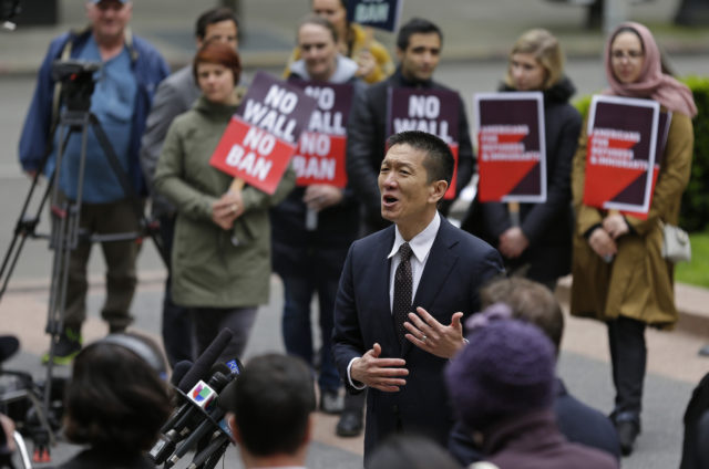 FILE - In this May 15, 2017, file photo, Hawaii Attorney General Doug Chin, center, talks to reporters outside a federal courthouse in Seattle. The fight over the latest version of President Donald Trump's travel ban that targets about 150 million potential travelers from Chad, Iran, Libya, North Korea, Somalia, Syria and Yemen returns to Washington state and Virginia. A three-judge panel of the 9th U.S. Circuit Court of Appeals hears arguments in Seattle on Wednesday, Dec. 6, followed by a full complement of 13 judges at the 4th Circuit in Richmond, Va., on Friday, Dec. 8. (AP Photo/Ted S. Warren, File)