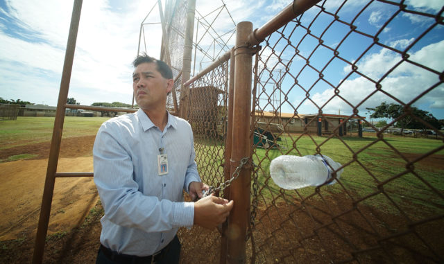 Campbell HS Principal Jon Henry Lee locks up the gate at Campbell High School baseball /softball field in Ewa.