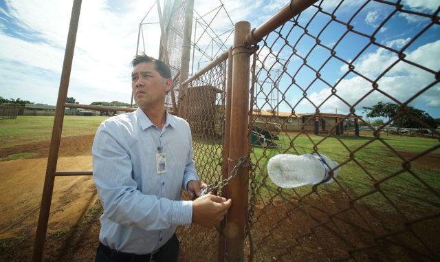 Campbell HS Principal Jon Henry Lee locks up the gate at Campbell High School baseball /softball field in Ewa.