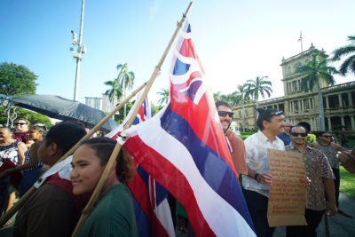 Olelo Hawaii demonstrators hold Hawaiian flags fronting Aliiolani Hale.