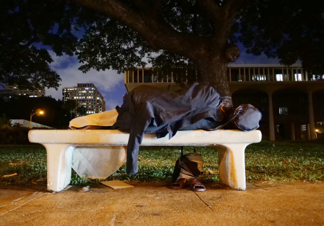 Person sleeps on bench Capitol Building Homeless at around 6am opening day of Legislature.