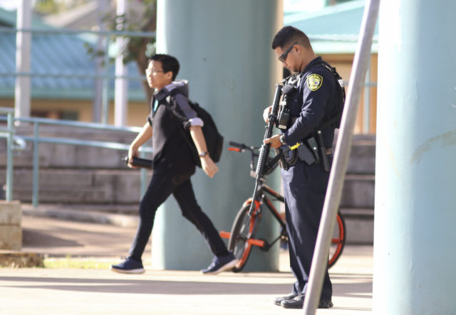 """A Honolulu police officer stands on the campus of Kapolei Middle School after a lockdown at the school was lifted, Friday, Feb. 16, 2018 in Kapolei, Hawaii. Hawaii Department of Education spokeswoman Donalyn Dela Cruz said school officials were notified of a threat Thursday night and reported it to police. The Honolulu Star-Advertiser reported someone posted on social media that they planned to """"shoot up"""" the middle school on Friday morning. (AP Photo/Caleb Jones)"""