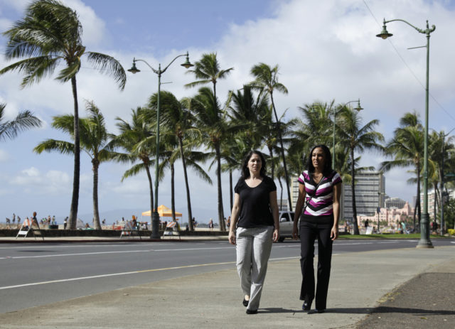 FILE - In this Dec. 19, 2011 file photo, Diane Cervelli, left, and Taeko Bufford, right, and walk past Waikiki beach in Honolulu. A Hawaii appeals court has ruled against a Hawaii bed and breakfast that denied two women a room because they're gay. The Intermediate Court of Appeals affirmed a lower ruling against Aloha Bed & Breakfast, whose owner appealed based on her religious views. (AP Photo/Eric Risberg, File)