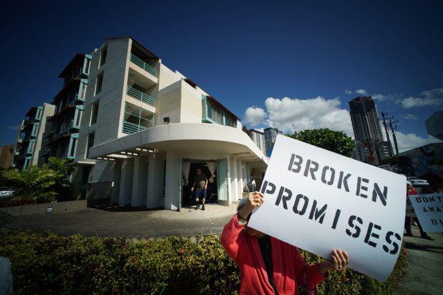 Na Lei Hulu Kupuna residents and supporters hold signs fronting their housing complex located in Kakaako.