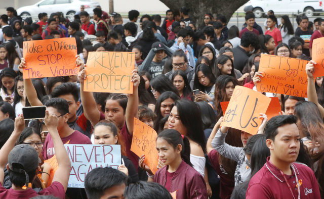 Farrington High School student hold signs before the moment of silence and the singing of Amazing Grace to honor students killed in the shooting at Marjory Stoneman Douglas High School in Parkland, Fla.