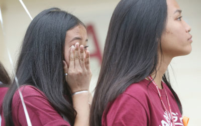 Farrington High School student wipes some tears during the singing of Amazing Grace after a moment of silence to honor students killed in the shooting at Marjory Stoneman Douglas High School in Parkland, Fla.