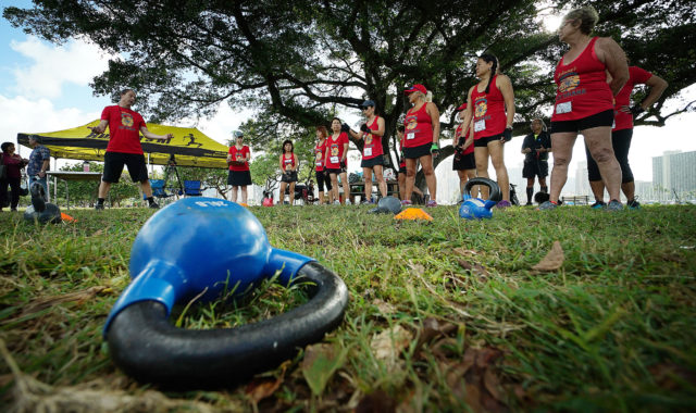 Dozene from Denby's kettlebell workout group from Johnny's Fitness Ohana get ready for their Guinness world record attempt with a kettlebell at left, Magic Island, Ala Moana Beach.