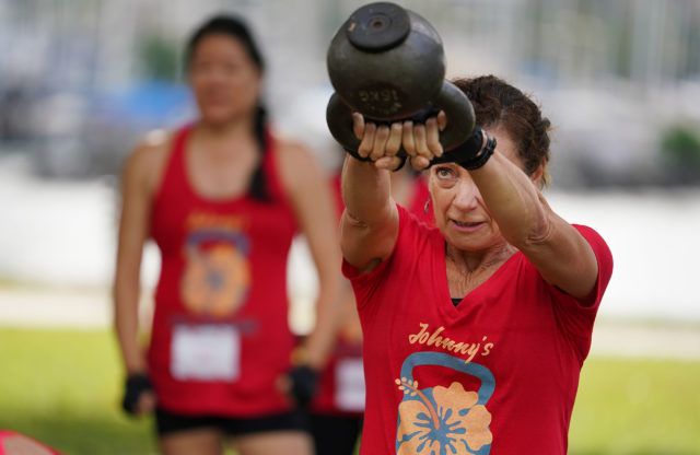 Twelve kettlebell workout group members from Johnny's Fitness Ohana lift their kettlebells attempt to beat the current record in the Guiness World Record at Magic Island.