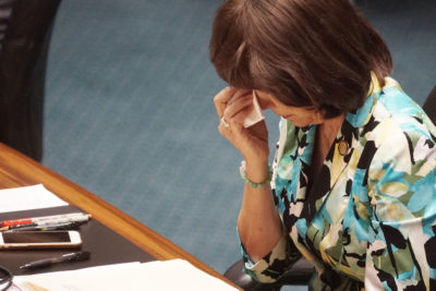 Senator Donna Mercado Kim wipes tears after sharing on the senate floor her history with the previous bills on physician assisted death bills.