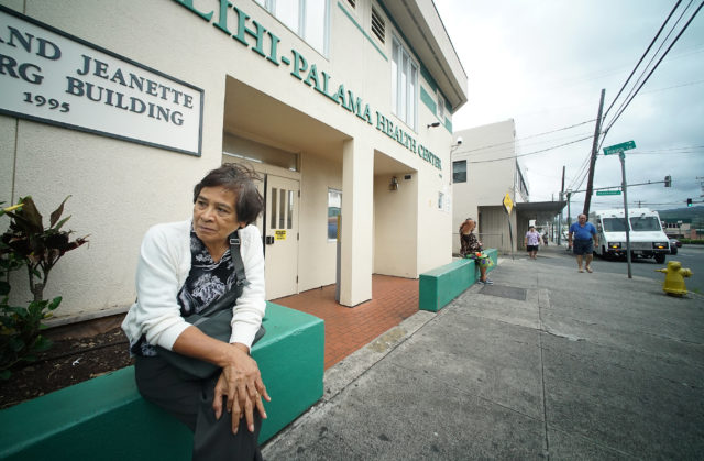 Kalihi resident Gertrude Aliado sits outside Kalihi Palama Health Center for dental services. Gertrude was waiting from 630am and the health center opened at at 8am.