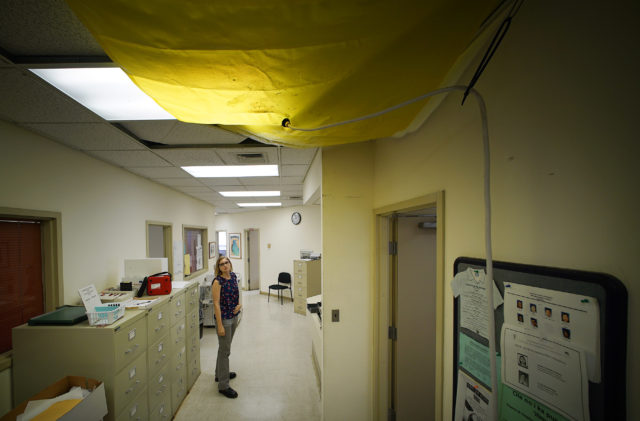 Medical Examiner Investigator Charlotte Carter walks past a portion of area on the 2nd floor of the building with yellow tarp material and leaky roof.