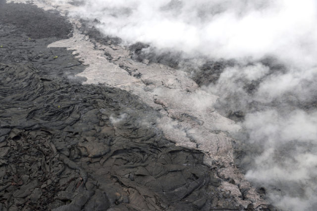 CORRECTS LOCATION TO HAWAII VOLCANOES NATIONAL PARK ON HAWAII'S BIG ISLAND - This May 1, 2018, photo provided by the U.S. Geological Survey shows a small lava flow (lighter in color) and spatter that erupted from a section of the crack on the west flank of Puu Oo vent of Kilauea Volcano in Hawaii Volcanoes National Park on Hawaii's Big Island. Dozens of earthquakes are rattling Hawaii's Kilauea Volcano as magma flows into a new area east of the Puu Oo vent. Officials with the U.S. Geological Survey's Hawaiian Volcano Observatory say the increased activity Wednesday, May 2, 2018, is associated with the collapse of the crater floor at the Puu Oo vent. (U.S. Gelological Survey via AP)