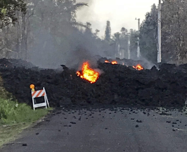 "This photo provided by Hawaii Electric Light shows lava flowing over Mohala Street in the Leilani Estates area near Pahoa on the Big Island of Hawaii Friday, May 4, 2018. Nearly 1,500 people have fled from their homes after Hawaii's Kilauea volcano sent molten lava chewing through forests and bubbling up on paved streets in an eruption that one resident described as ""a curtain of fire."" (Hawaii Electric Light via AP)"