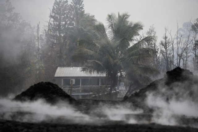 Toxic gases rise near an abandoned home in the Leilani Estates subdivision near Pahoa, Hawaii Friday, May 18, 2018. Hawaii residents covered their faces with masks after a volcano menacing the Big Island for weeks exploded, sending a mixture of pulverized rock, glass and crystal into the air in its strongest eruption of sandlike ash in days. (AP Photo/Jae C. Hong)