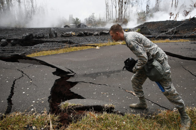 U.S. Air National Guardsman John Linzmeier looks at cracks as toxic gases rise near by in the Leilani Estates subdivision near Pahoa, Hawaii Friday, May 18, 2018. Hawaii residents covered their faces with masks after a volcano menacing the Big Island for weeks exploded, sending a mixture of pulverized rock, glass and crystal into the air in its strongest eruption of sandlike ash in days. (AP Photo/Jae C. Hong)