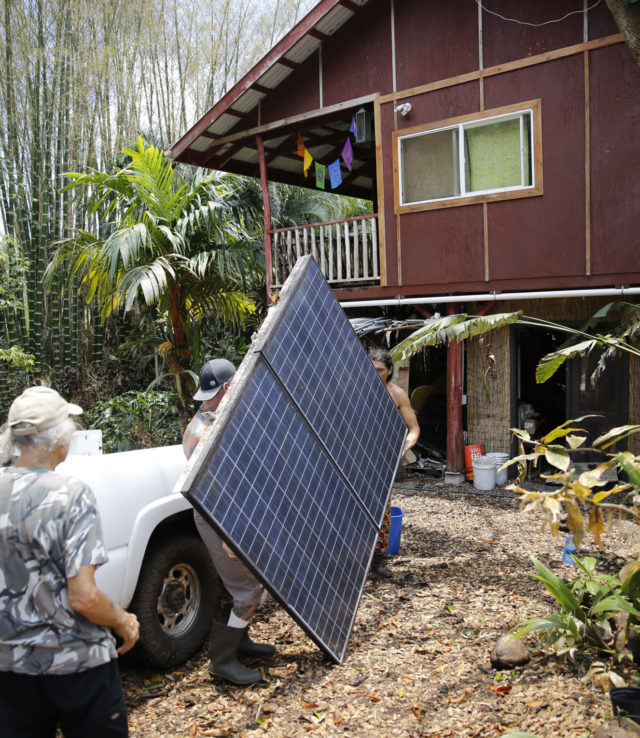Edwin Montoya, left, watches Mike Guich, center, and Abe Pedro, load a solar panel removed from the Montoya family's property, onto a truck, Friday, May 18, 2018, near Pahoa, Hawaii. The Montoya family owns a farm near Pohoiki Road and lava crossed the road near his property, Friday, blocking off access. (AP Photo/Marco Garcia)