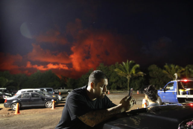 Evacuee Michael Hauanao, 32, watches a clip on a phone showing volcano activities at a makeshift donation center as clouds turn red from lava flow in the Leilani Estates subdivision near Pahoa, Hawaii Friday, May 18, 2018. Hawaii residents covered their faces with masks after a volcano menacing the Big Island for weeks exploded, sending a mixture of pulverized rock, glass and crystal into the air in its strongest eruption of sandlike ash in days. (AP Photo/Jae C. Hong)