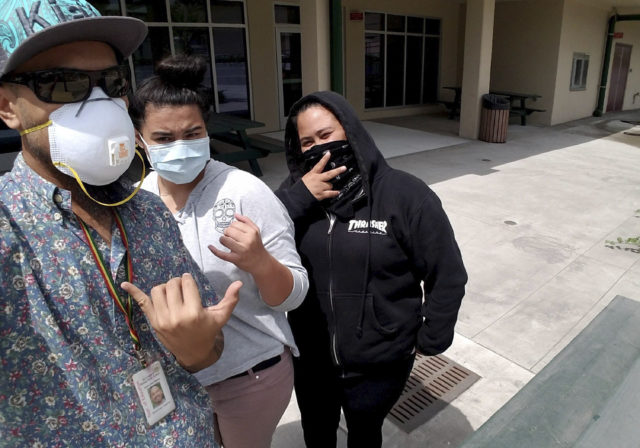 In this Wednesday, May 23, 2018 photo provided by teacher Aina Akamu, Akamu, at left, takes a photo with his students, Shyann Tamura, center, and Shyanne Akiona, right, at their school campus in Pahala, Hawaii. Kau High and Pahala Elementary School were covered in ash that spewed out of a Hawaii volcano explosion and drifted down into their small and rural town. School officials have been handing out ash-filtering face masks. (Aina Akamu via AP)