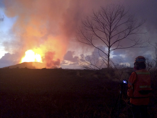 In this photo provided by the U.S. Geological Survey, crews make visual observations of lava activity at fissure 8, Thursday, May 31, 2018 near Pahoa, Hawaii. Fountain heights Thursday morning continued to reach 230 to 260 feet (70 to 80 meters) above ground level. The fountaining feeds a lava flow that is moving to the northeast along Highway 132 into the area of Noni Farms road. (U.S. Geological Survey via AP)