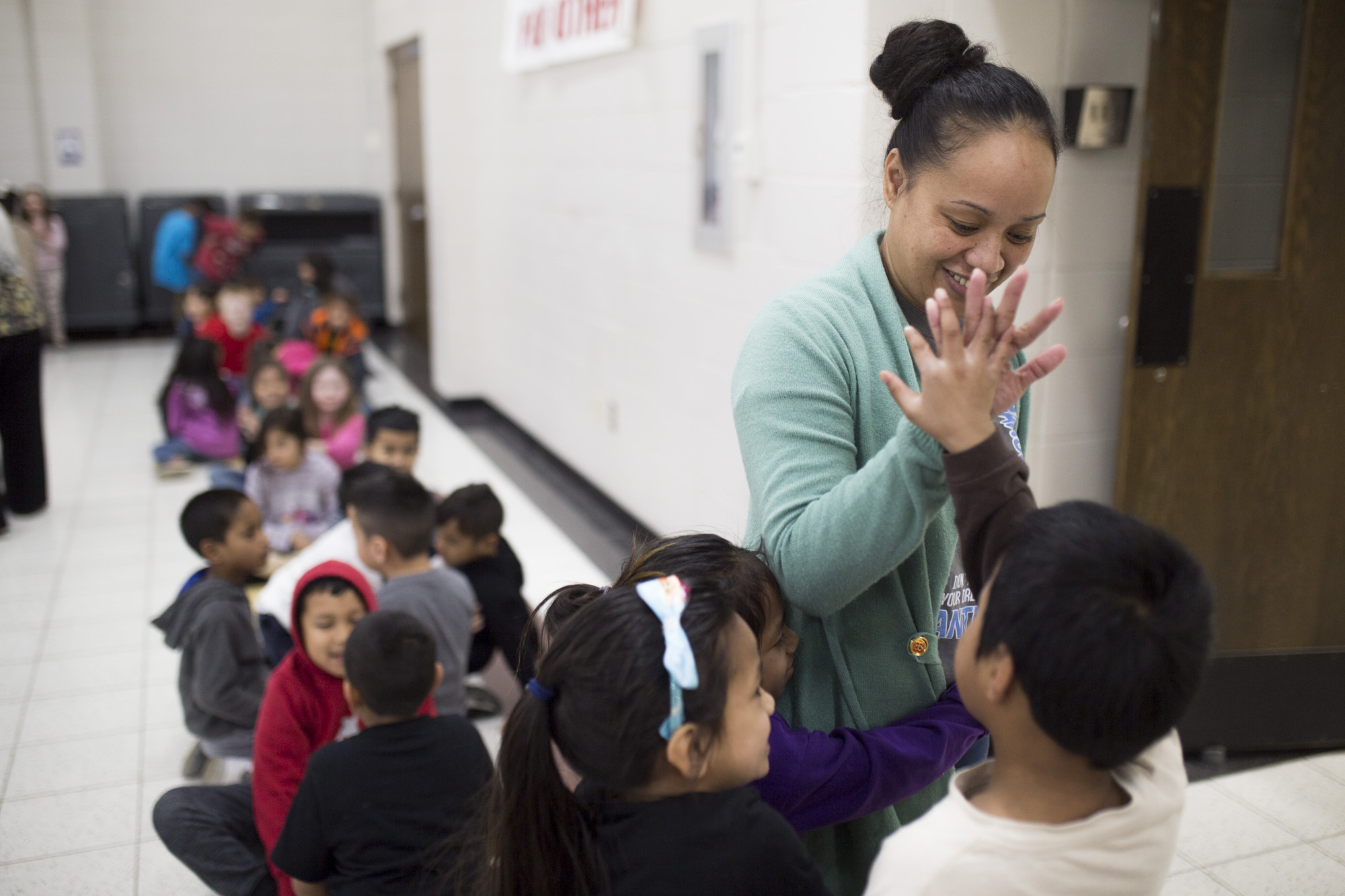 Marshallese Liason Carlins Jerry high-fives a student (XXXXX) at Parson Hills Elementary School in Springdale, February 13, 2018.