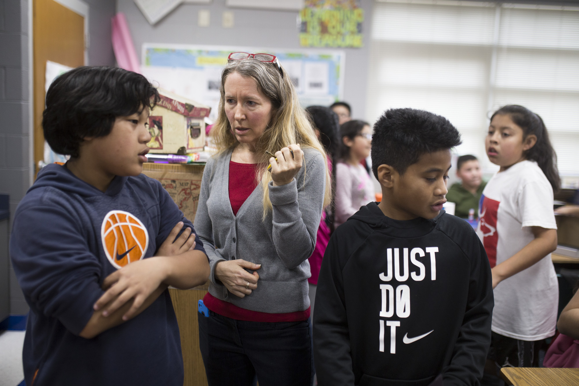 ESL Instructional Facilitator Deanna Self (center) helps Marshallese student Mackson Kaminaga 11 (left) on a project as Gabriel Labin 10 walks by at their fifth grade class at Robert E. Lee Elementary School in Springdale, February 14, 2018.