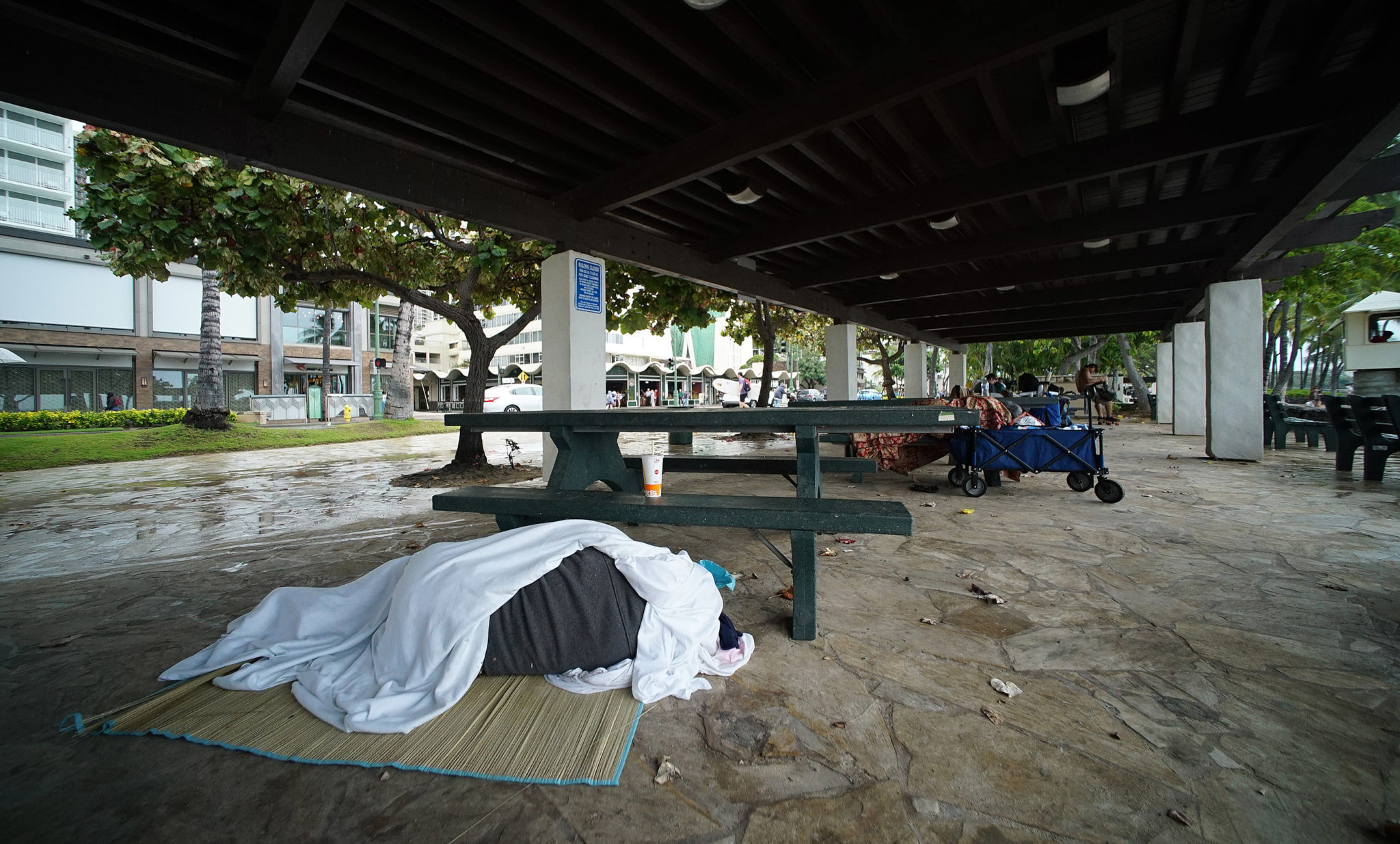 Kalakaua Avenue covered pavillions with sleeping person on mat near Lifeguard tower 2C.